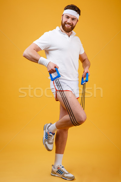 Portrait of a sporty man exercising with rubber expander Stock photo © deandrobot