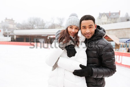 Young cheerful loving couple skating at ice rink outdoors. Stock photo © deandrobot