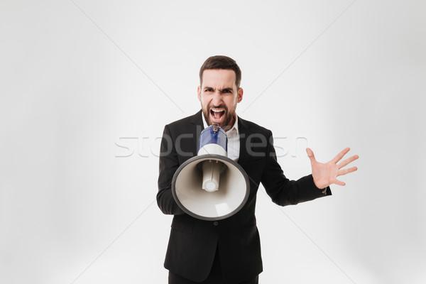 Screaming businessman talking with loudspeaker. Stock photo © deandrobot