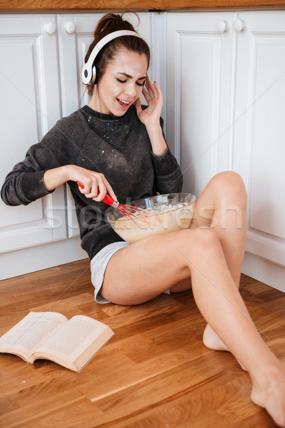 Young pretty girl in headphones singing and blending dough Stock photo © deandrobot