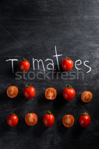 Picture of cut tomatoes over dark background Stock photo © deandrobot
