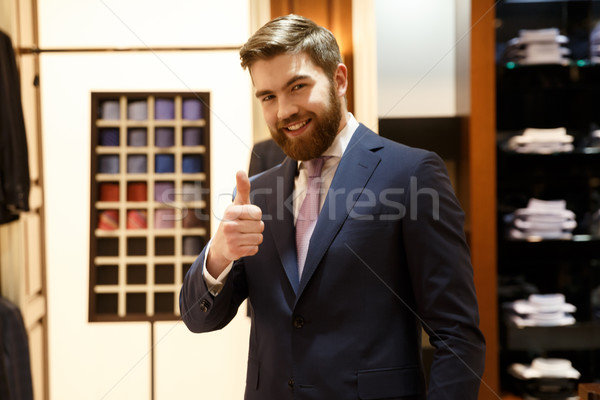 Smiling man showing thumb up Stock photo © deandrobot