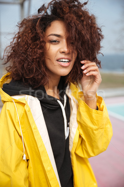 Amazing african curly young woman wearing yellow coat Stock photo © deandrobot