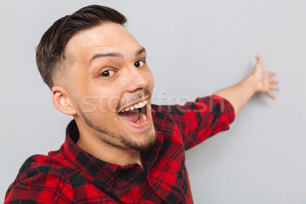 Happy  man standing sideways and posing in studio Stock photo © deandrobot
