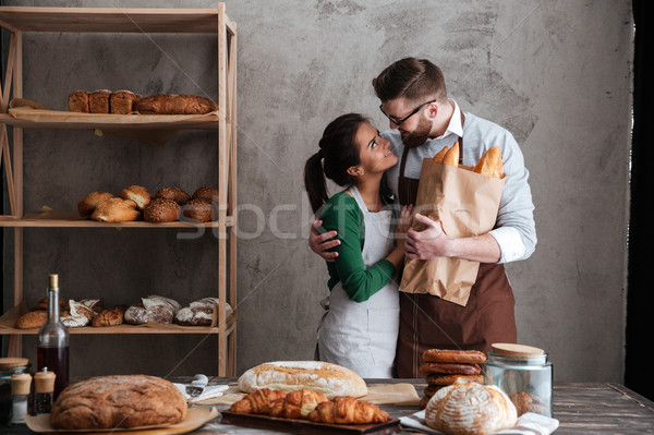 Cheerful loving couple bakers standing near bread Stock photo © deandrobot