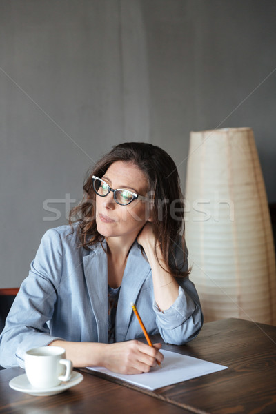 Thoughtful woman writer sitting indoors Stock photo © deandrobot