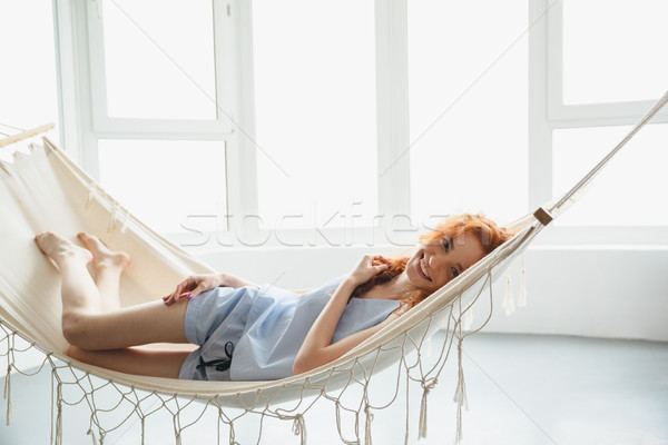 Cute cheerful young redhead lady lies on hammock Stock photo © deandrobot