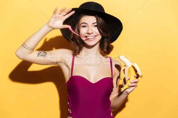 Playful girl in beachwear chewing bubble gum and holding banana Stock photo © deandrobot
