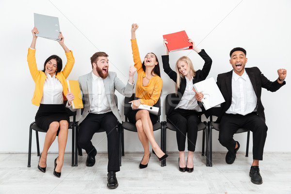 Cheerful colleagues sitting in office holding folders. Stock photo © deandrobot