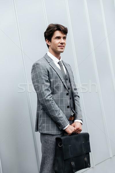 Yakışıklı işadamı takım elbise ayakta evrak çantası beyaz Stok fotoğraf © deandrobot