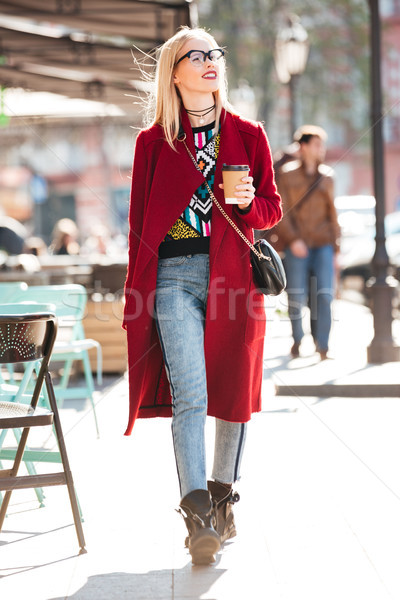 Amazing young caucasian woman walking outdoors drinking coffee. Stock photo © deandrobot