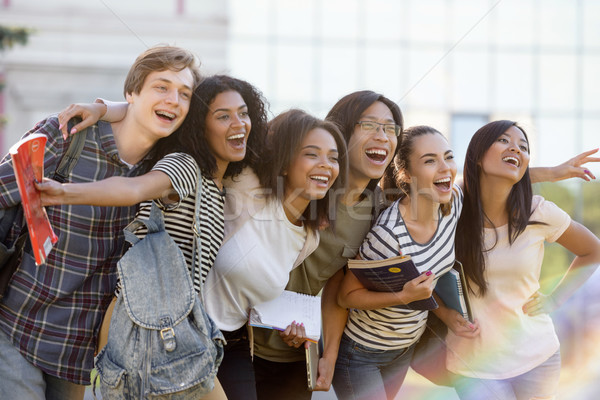 Multiethnic group of young happy students standing outdoors Stock photo © deandrobot