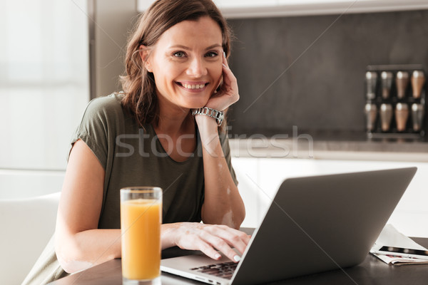 Happy casual woman sitting by the table with juice Stock photo © deandrobot