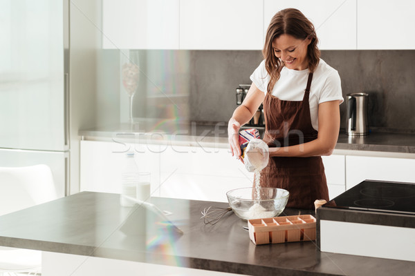 Smiling casual woman cooking near the table Stock photo © deandrobot