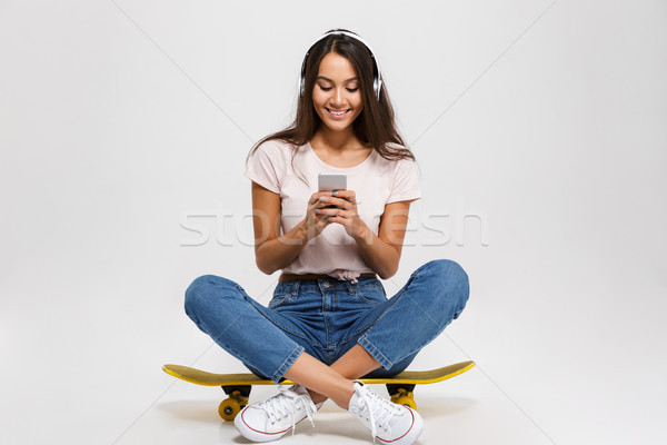 Portrait of young smiling girl in white headphone chatting by ph Stock photo © deandrobot