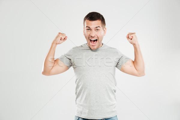 Boldog sikít férfi mutat bicepsz néz Stock fotó © deandrobot