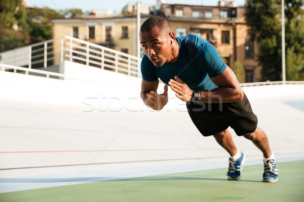 Portrait of a fit afro american sportsman doing push-ups Stock photo © deandrobot