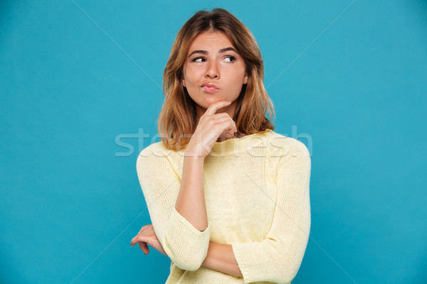 Pensive woman in sweater holding her chin and looking away Stock photo © deandrobot