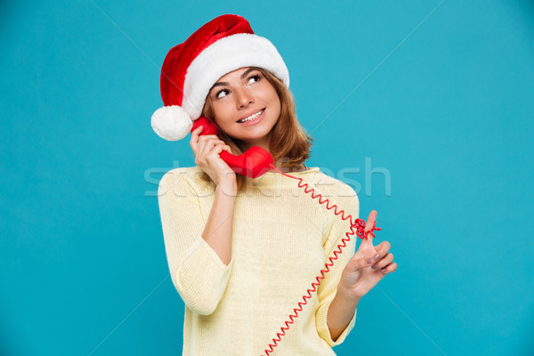Close-up photo of beautiful young woman in Santa's hat playing with red cord while talking on retro  Stock photo © deandrobot