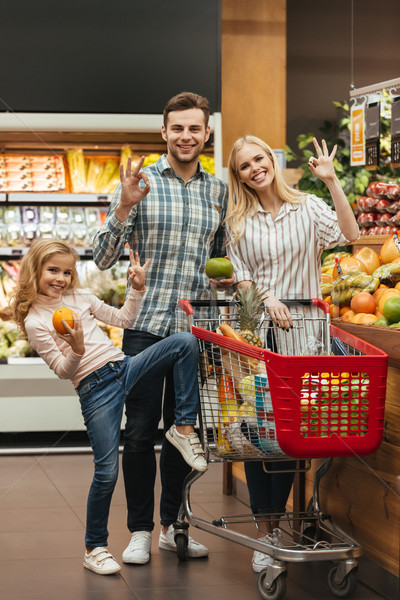 Happy family choosing groceries and showing ok gesture Stock photo © deandrobot