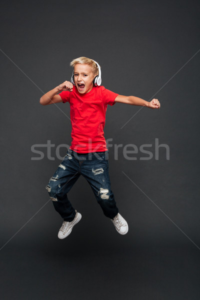 Excited little boy child jumping listening music with headphones. Stock photo © deandrobot