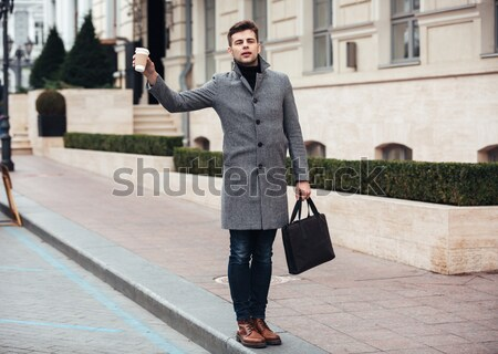 Picture of handsome businessman with takeaway coffee in hand, cr Stock photo © deandrobot
