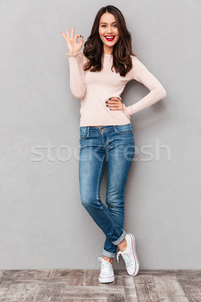 Full-length image of gorgeous female in jeans smiling and gestur Stock photo © deandrobot