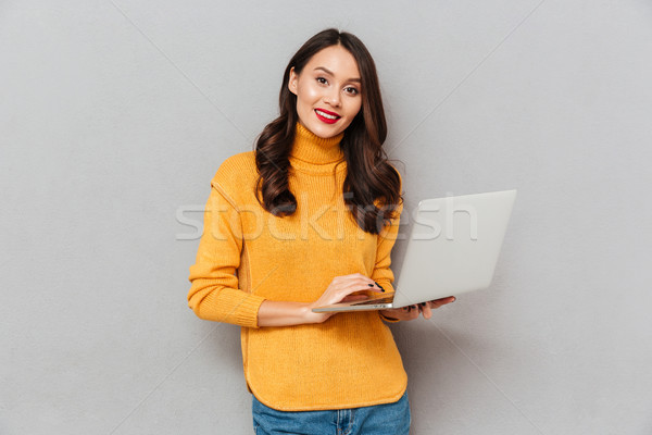 Pleased brunette woman in sweater holding laptop computer Stock photo © deandrobot
