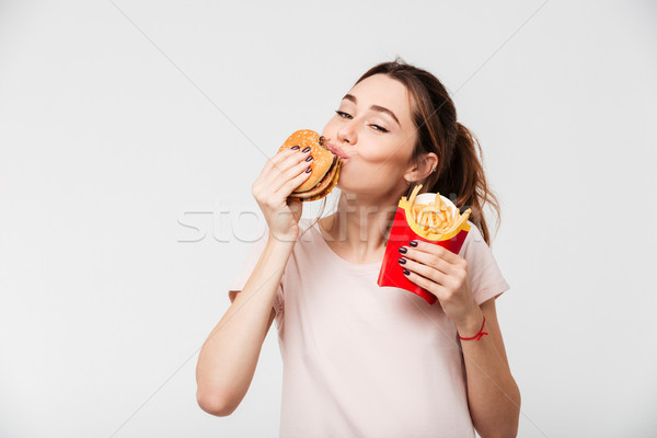 Close up portrait of a satisfied girl eating french fries Stock photo © deandrobot