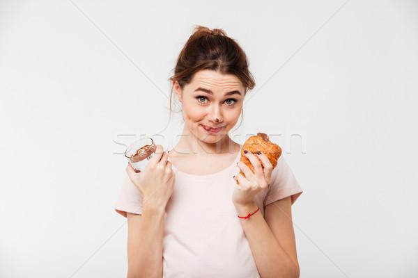 Portret glimlachend mooie meisje eten croissant Stockfoto © deandrobot