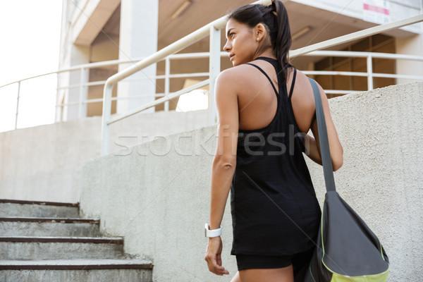 Hátulnézet fiatal nő sportruha hordoz táska sétál Stock fotó © deandrobot