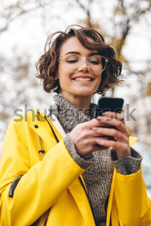 Amazing young woman dressed in raincoat Stock photo © deandrobot