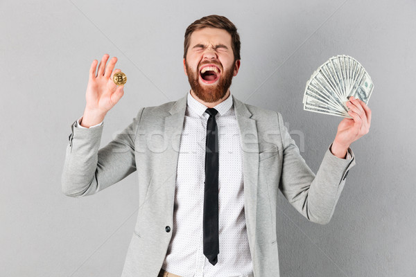 Portrait of a satisfied businessman showing bitcoin Stock photo © deandrobot