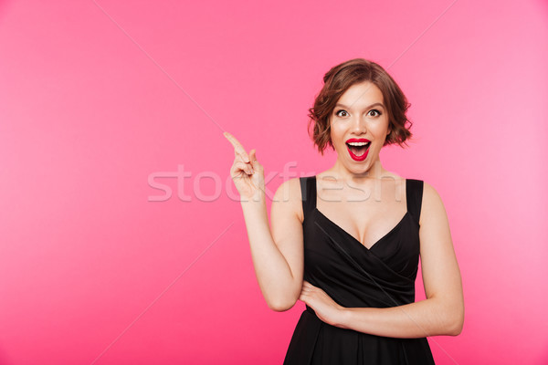 Portrait of an excited girl dressed in black dress Stock photo © deandrobot