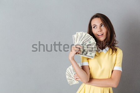 Contented nice woman rejoicing her purchases holding fan of 100  Stock photo © deandrobot