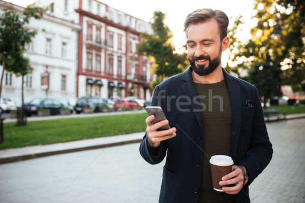 Portrait of a young man holding mobile phone Stock photo © deandrobot