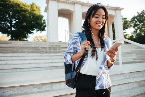 Fiatal ázsiai nő csíkos póló telefon Stock fotó © deandrobot