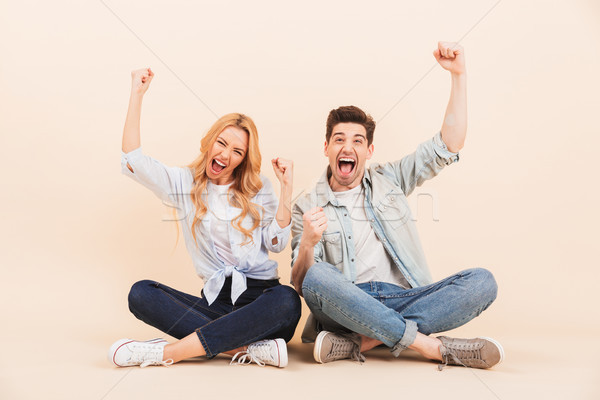 Image of happy two friends man and woman screaming and rejoicing Stock photo © deandrobot