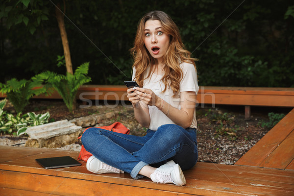 Stock photo: Surprised young girl holding mobile phone