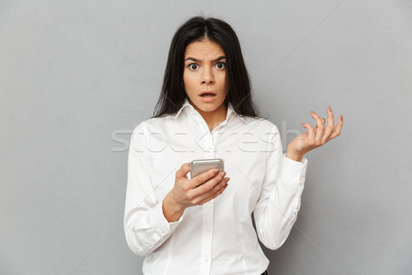 Photo of shocked or outraged woman 30s in formal wear looking on Stock photo © deandrobot