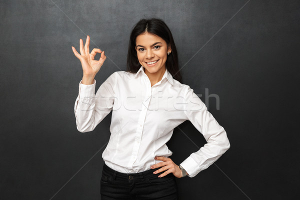 Portrait of business young woman wearing white shirt showing ok  Stock photo © deandrobot