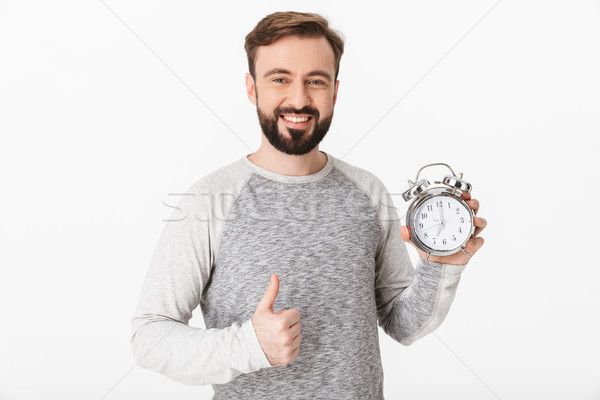 Happy young man holding alarm clock showing thumbs up. Stock photo © deandrobot