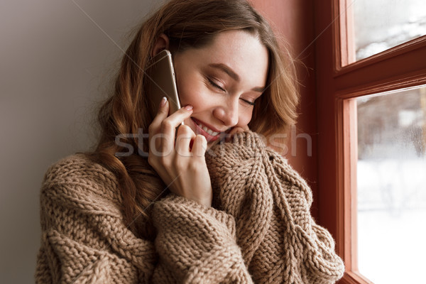 Cute pleased woman 20s with brown hair holding phone, and enjoyi Stock photo © deandrobot