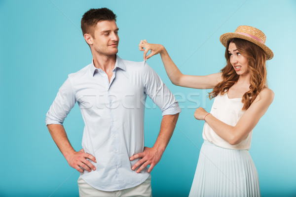 Young caucasian woman displeased because of man's shirt Stock photo © deandrobot