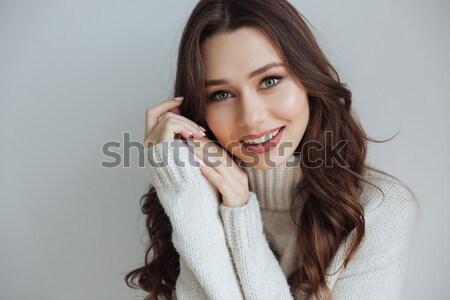 улыбаясь брюнетка женщину свитер прослушивании музыку Сток-фото © deandrobot