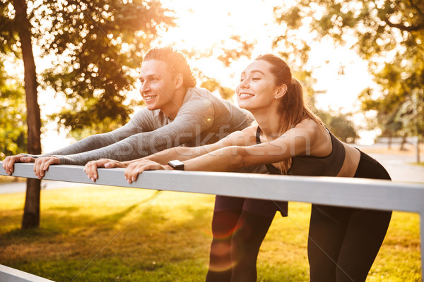 Stock photo: Fitness sport loving couple friends in park outdoors make sport exercises.