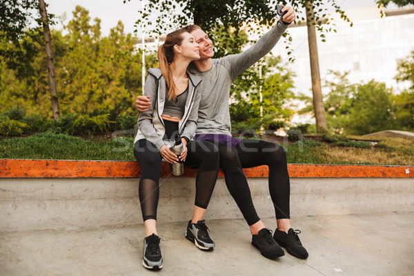 Image of young sporty couple man and woman 20s in tracksuits, si Stock photo © deandrobot