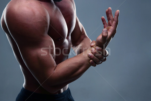 Stock photo: Muscular man with hand pain on gray background