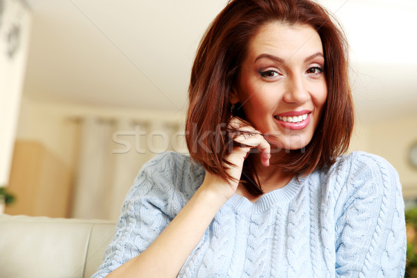 Portrait of a smiling woman on the sofa at home Stock photo © deandrobot