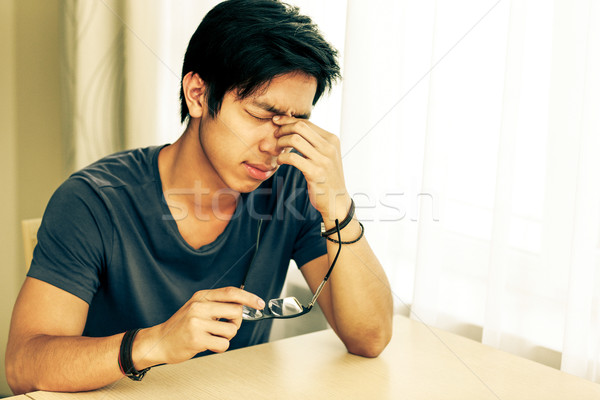 Tired asian man with eye pain holding glasses in hand Stock photo © deandrobot